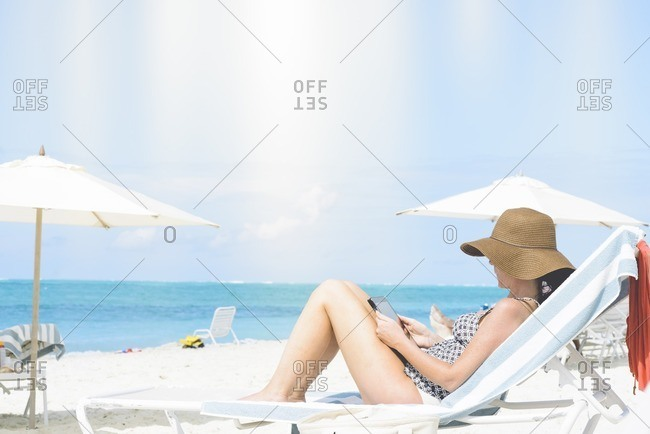 Woman relaxing with a tablet on a beach lounge chair