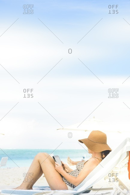 Woman reading a tablet on a beach lounge chair