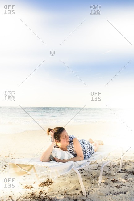Woman relaxing on a lounge chair at the beach