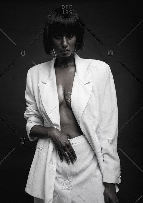 Woman wearing white suit with hand in her pants