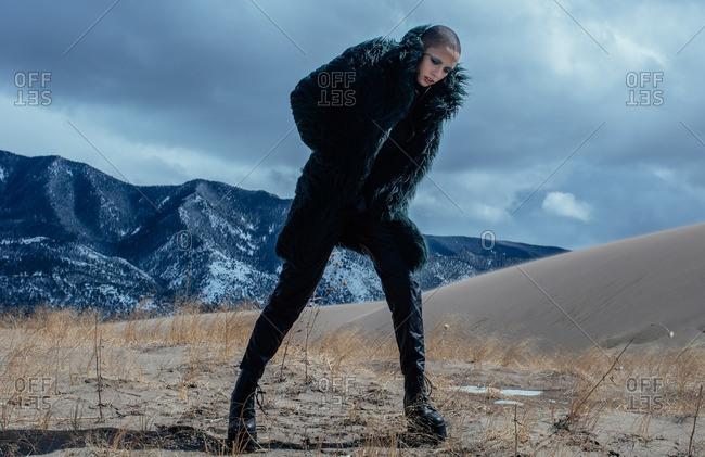 April 17, 2016: Woman wearing black fur coat by mountains