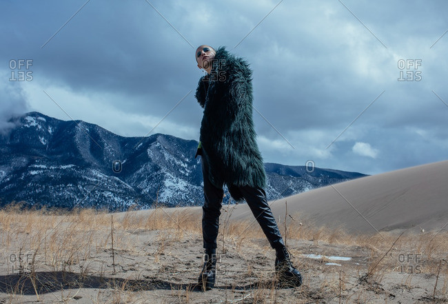April 17, 2016: Woman wearing black fur coat in mountain setting