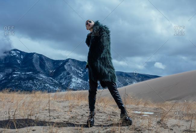 April 17, 2016: Woman wearing black fur coat in mountain setting