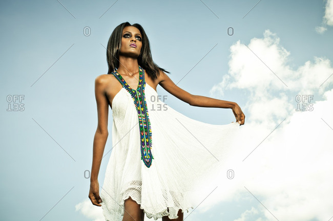 April 23, 2012: Woman lifting skirt of her white dress in front of cloudy sky