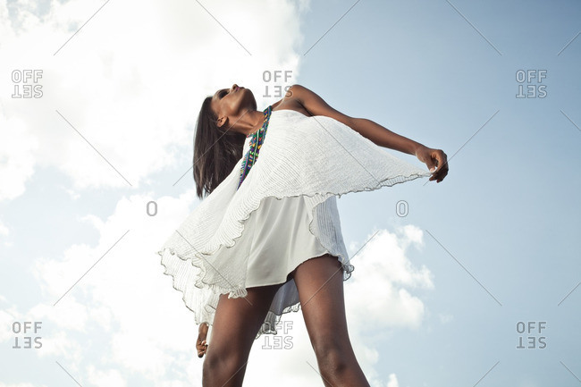 April 23, 2012: Low angle view of woman in white dress in front of cloudy sky