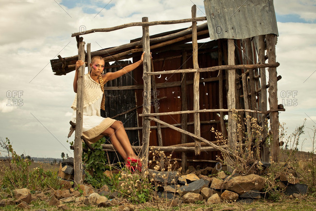 April 28, 2012: African woman sitting on wooden structure