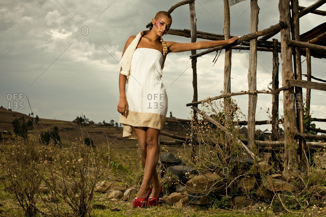 April 28, 2012: Woman wearing white dress holding onto wooden structure