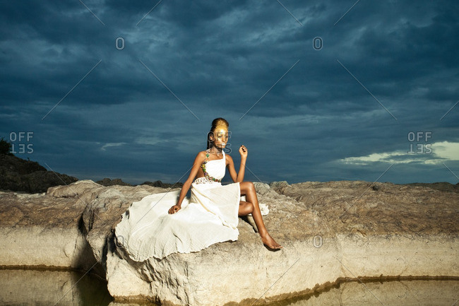 April 28, 2012: Woman wearing white dress and gold makeup on top of mountain