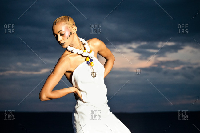 April 28, 2012: Bald woman wearing white dress with hands on her hips
