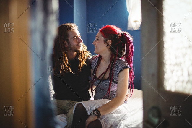 Young hipster couple sitting on bed at home
