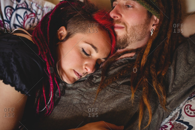 Young hipster couple relaxing on bed at home