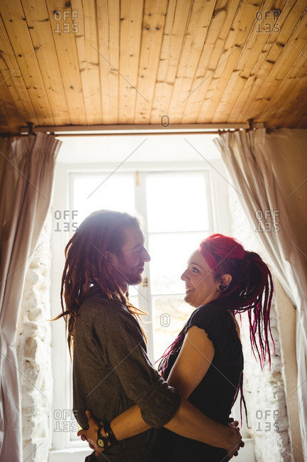 Happy young couple romancing against window at home