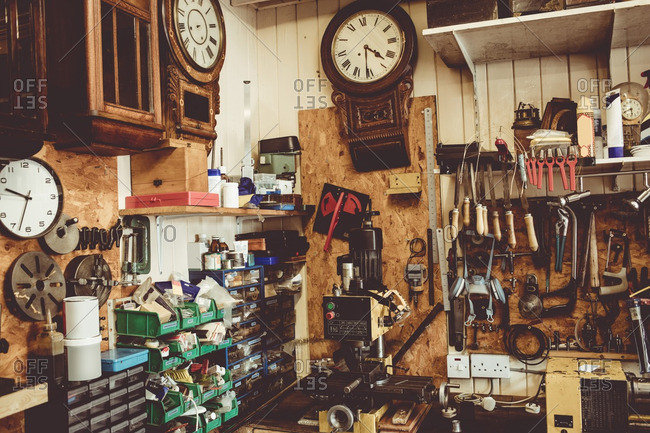 Old horologists workshop with clock repairing tools, equipment and clocks on the wall