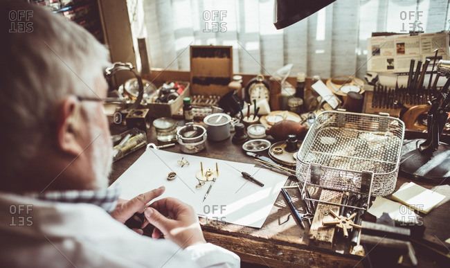 Rear view of horologist repairing an watch in the workshop