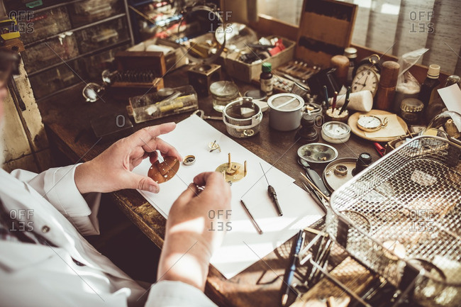 Mid section of horologist repairing a watch in the workshop
