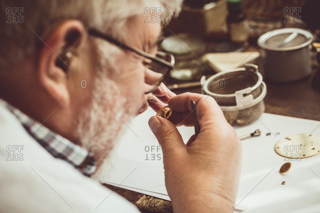 Rear view of horologist repairing a watch in the workshop