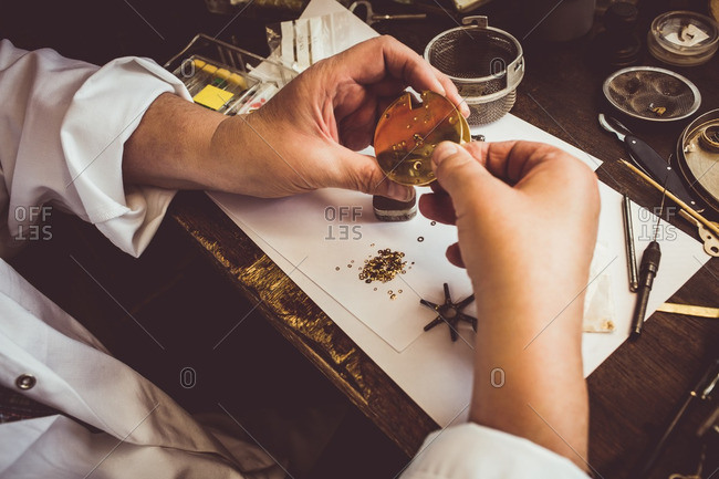 Hands of horologist repairing a watch in the workshop