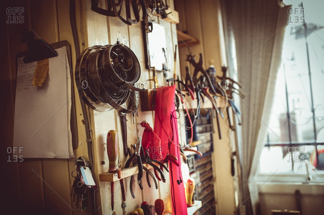 Old horologists workshop with clock repairing tools and equipment on wall