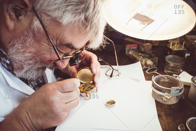 Horologist repairing a pocket watch in the workshop