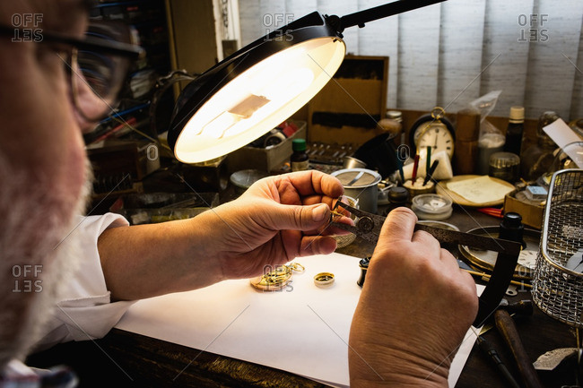 Close-up of horologist repairing an watch in the workshop