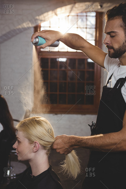 Male hairdresser styling customers hair with hair spray at a salon