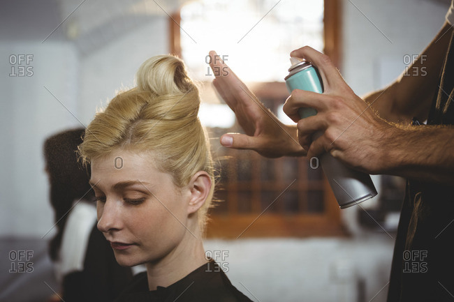 Hairdresser styling customers hair with spray in salon