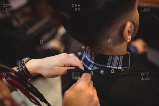 Female barber removing client apron in barber shop