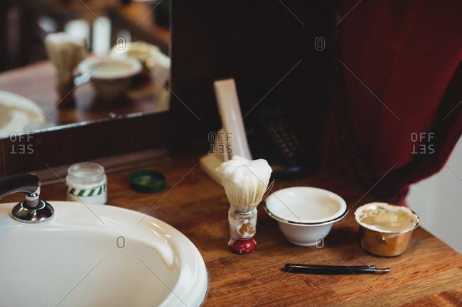 Wash basin, shaving brush, razor and bowl on wooden table in barber shop