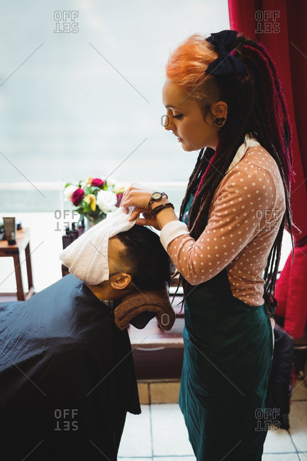 Barber applying a hot towel on a client face in barber shop