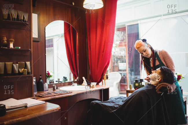 Man getting his beard shaved with shaving brush in barber shop