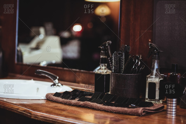 Barber spray bottle, brush and accessory on dressing table in barber shop