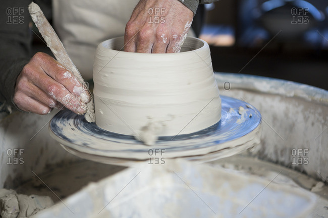 Mid section of potter making pot in pottery workshop