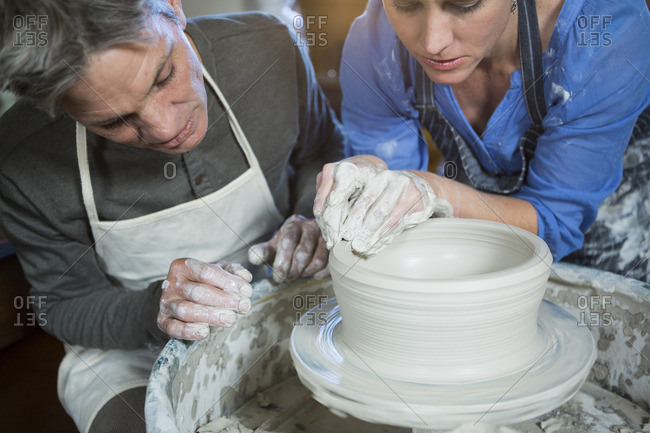 Male potter assisting female potter in pottery workshop