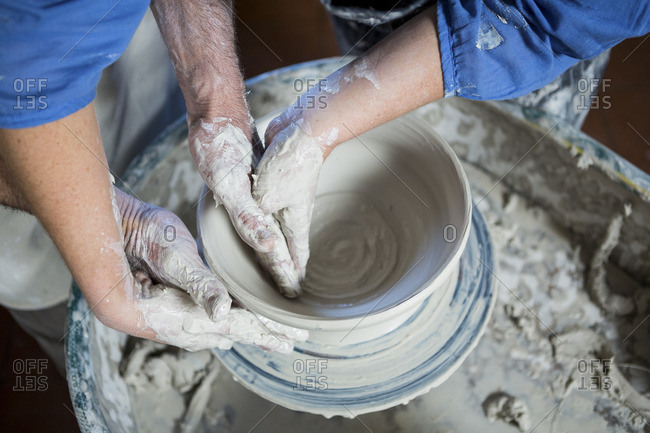 Mid section male potter assisting female potter in pottery workshop