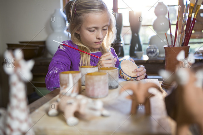 Attentive girl painting on bowl in pottery workshop