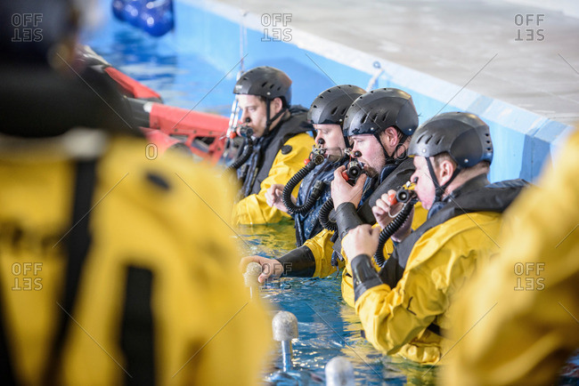Offshore oil workers being trained in survival techniques in pool facility