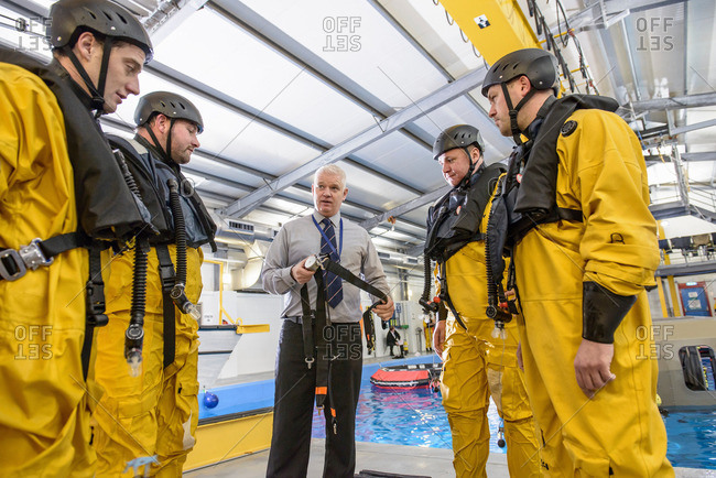 Tutor teaching offshore oil workers survival training in pool facility