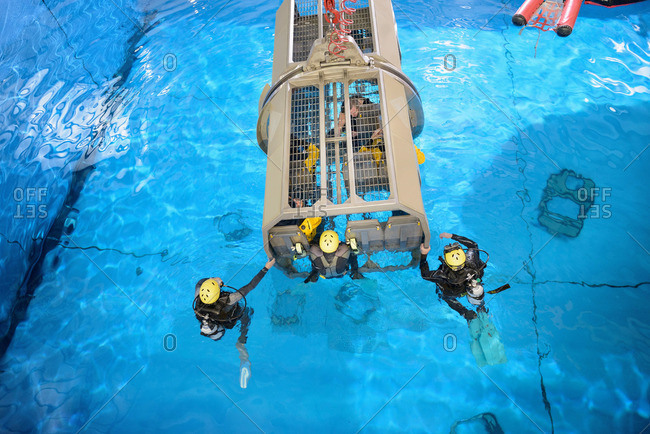 Offshore oil workers in simulated helicopter, being trained in sea ditching survival in pool facility