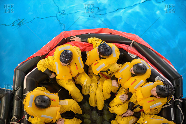 Above view of an offshore oil workers in raft being trained in sea ditching survival in pool facility