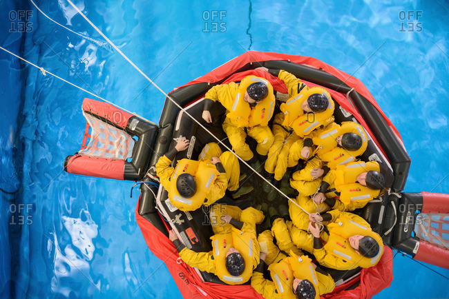 Overhead view of an offshore oil workers in raft being trained in sea ditching survival in pool facility