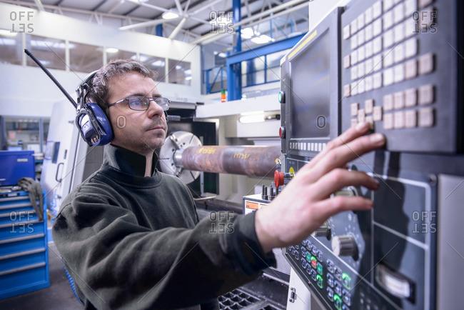 Engineer in ear defenders setting controls on industrial lathe