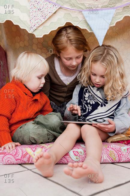 Children using tablet computer in fort