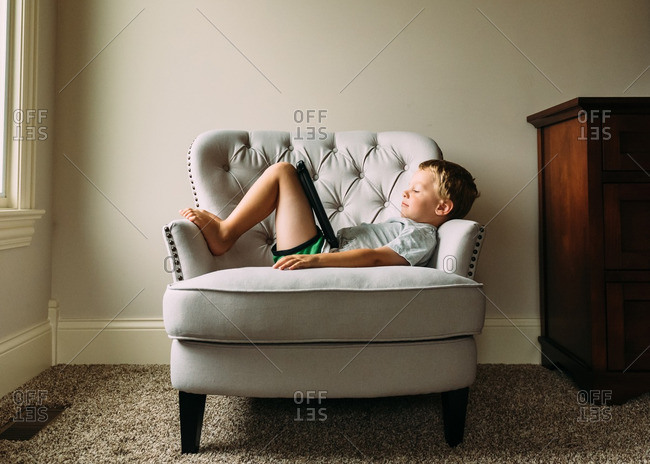 Boy laying in chair watching tablet