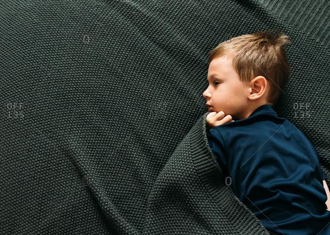 Boy lying with a blanket
