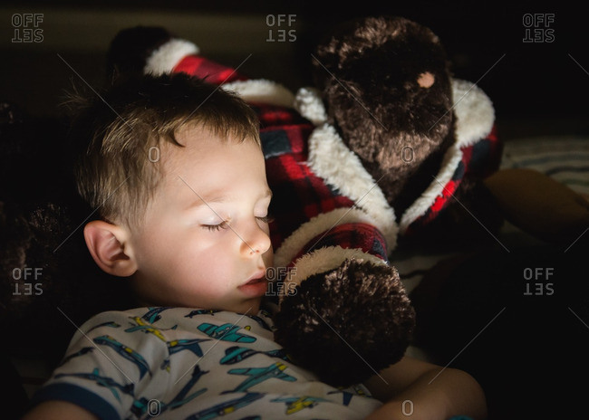 Boy napping with teddy bear