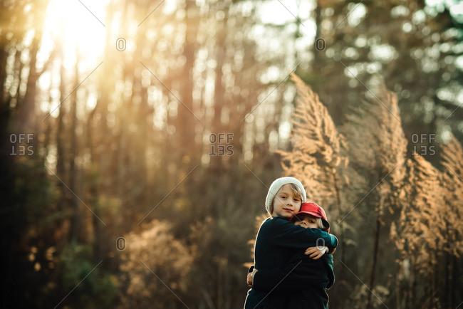 Boys hugging in fall countryside