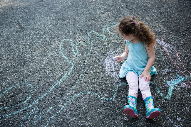 Girl sitting drawing with chalk