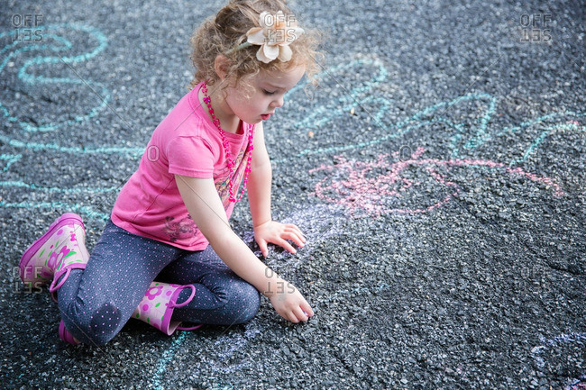 Girl on ground drawing with chalk