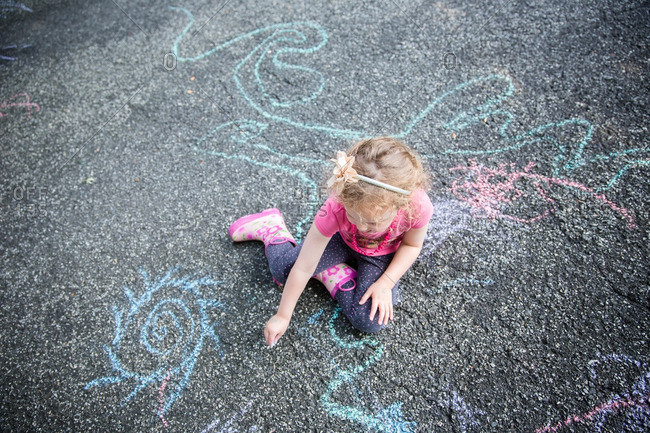 A girl chalk drawing on pavement