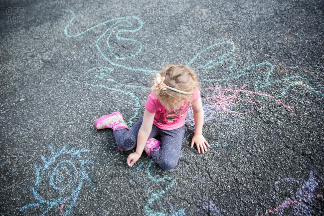 A girl drawing with chalk on pavement